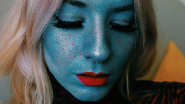 blue alien face with red freckles and red lips